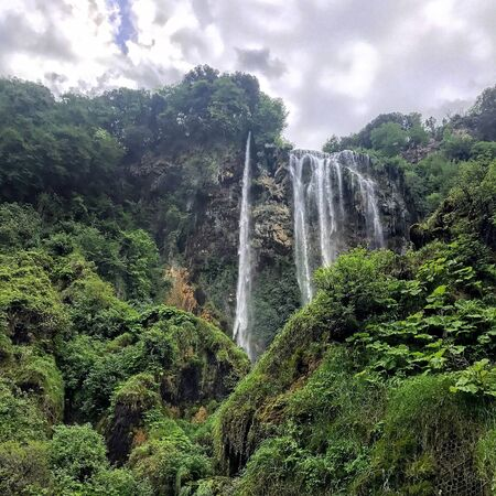 Lush green mountainous area with water falling from above