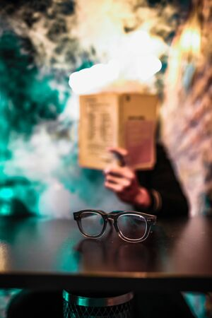 A pair of eyeglasses sit unused on a table as a person reads a book. Stockfoto