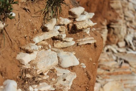 Stone rocks sticking out of a dirt wall. Stock Photo