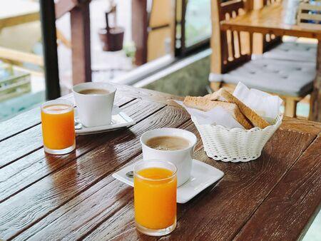 beverage filled mugs and drinking glasses and slice breads in basket on wooden tabke