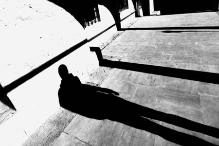 grayscale photography of person's shadow on concrete pavement