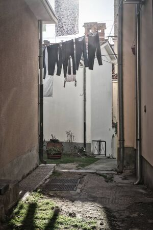 Clothes hang from clotheslines at the mouth of a small dirt alleyway.