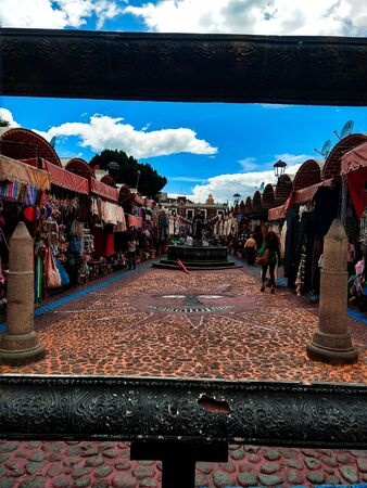 Market stalls lined on both sides of an inlaid walkway.