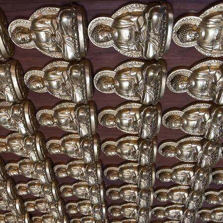 silver-colored Buddha figurines on wall Banco de Imagens