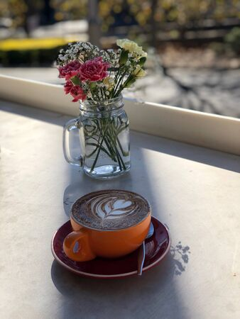 orange and black ceramic mug with saucer filled with coffee
