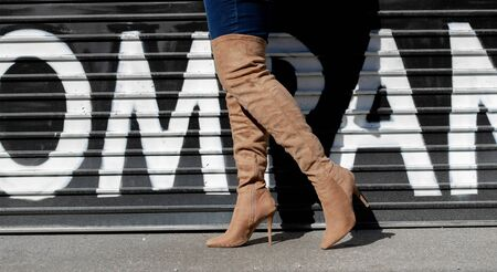 person wearing blue suede stiletto boots walking on pavement
