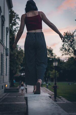 woman walking on concrete pavement near green field