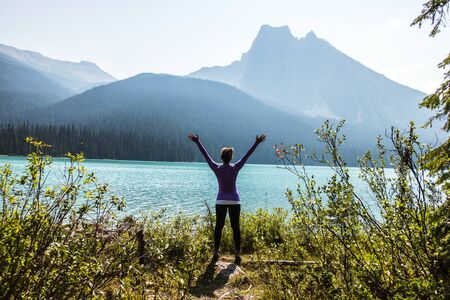 woman standing and raising both hands beside plants and facing the lake during day Imagens