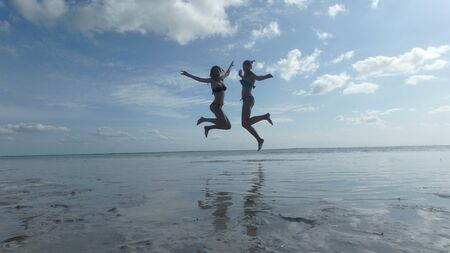 two girl jumping above water