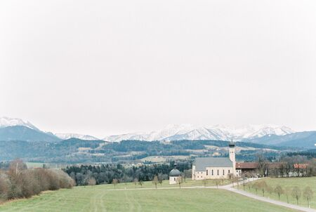 white and gray church on grass field beside mountain