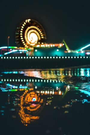 reflection of Ferris wheel on body o fwater at night