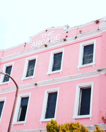 Pink and white painted the arcade building Imagens
