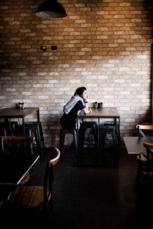person sitting beside table Imagens