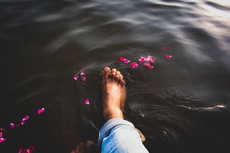 right foot on body of water with red flower Banco de Imagens