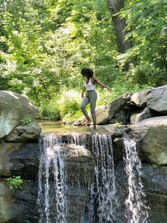 woman walking on river near waterfalls