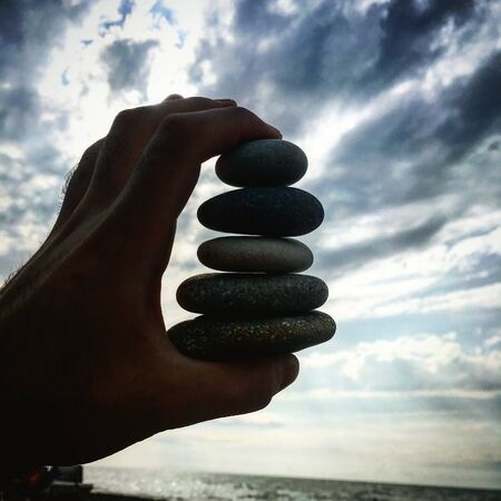 Person holding stack of five stones Stok Fotoğraf