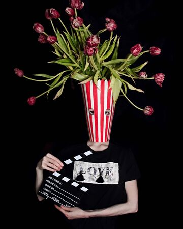 A person wearing a vase full of flowers as a mask and headress 版權商用圖片