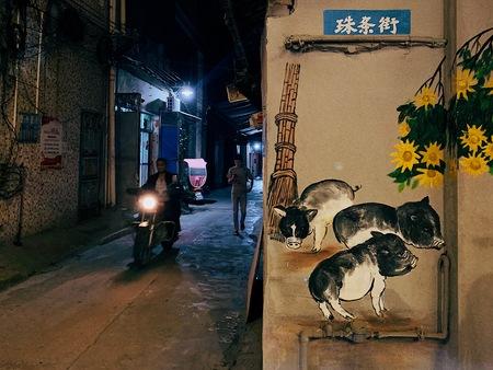 man riding motorcycle passing man walking on street during night time