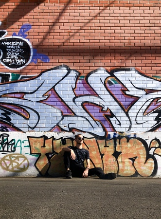 man in black shirt sitting and leaning on wall with graffiti Editorial