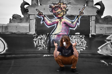 man on black t-shirt and brown pants kneeling near wall with graffiti Editorial