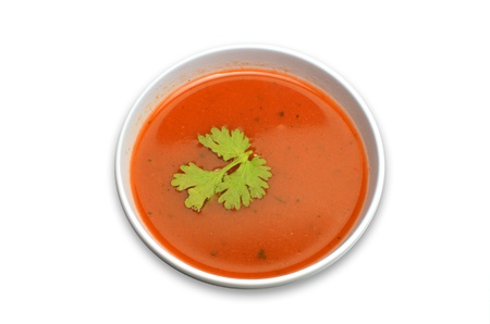 A bowl of hot tomato soup garnished with coriander isolated on white photo