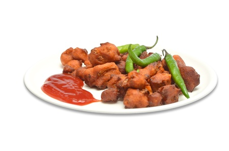 A plate of fresh onion pakoras garnished with green chilies and tomato ketchup photo