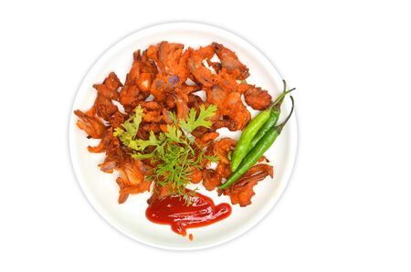 A plate of fresh cauliflower pakoras garnished with coriander, green chilies and tomato ketchup photo