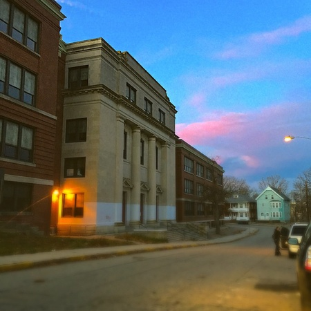 glow: Pink Sunset on the horizon behind the Woonsocket, RI Middle School in late Autumn