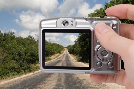 Digital camera in a hand. Photo on screen and background is my own shot Foto de archivo
