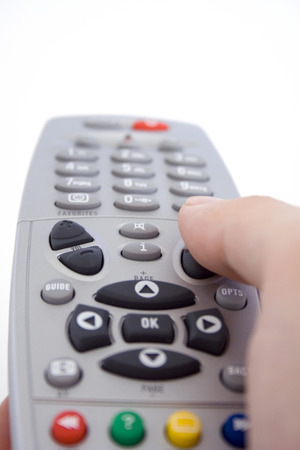 A hand holding a TV remote control