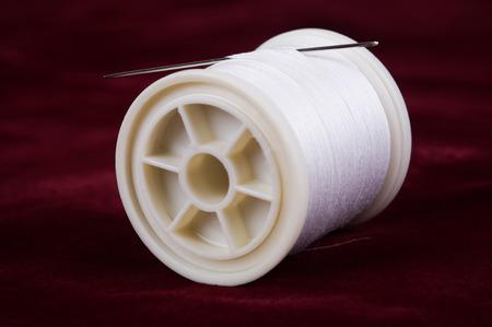 Thread with needle on velvet red background