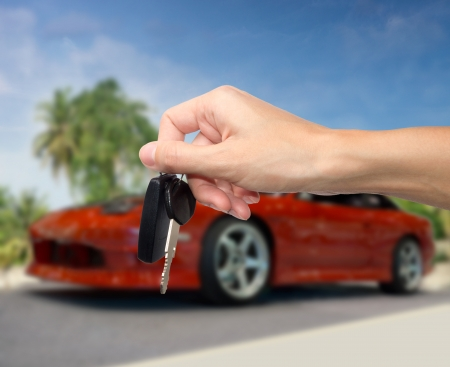 Hand holding key against new car photo