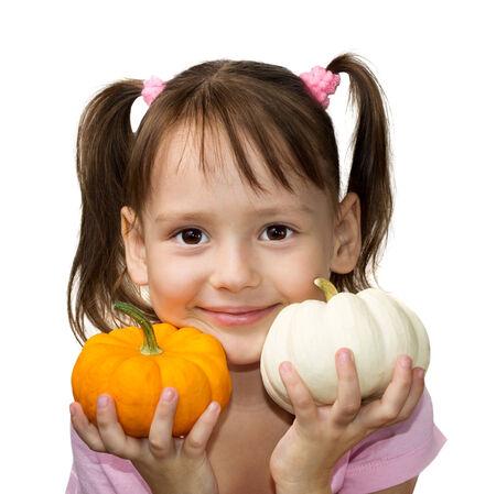 Cute little girl holding pumpkins