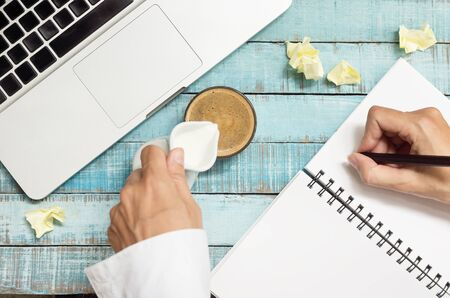 coffe break: hands pouring milk in coffe cup and writing in notebook on workplace. Coffee break concept. Hands in frame.