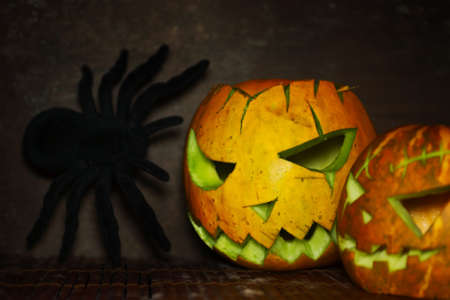 wood spider: Scary pumpkin lantern with spider on wood. Halloween background, text space Stock Photo