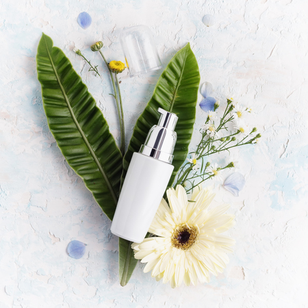 Flat lay facial moisturizing cream on tropical leaves and flowers. Healthy lifestyle, body care concepr. Bright beauty product background Banque d'images