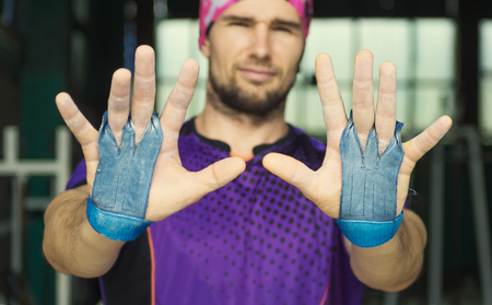 callus: young muscular hipster athlete shows palm protection grips on his hands. Crossfit, fitness, bodybuilding concept. Focus on palms. Sport equipment Stock Photo