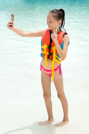 Smiling Preteen girl in life vest takes selfie by cell phone camera. Blurred water in background. Safe vacation, insurance concept Stock Photo