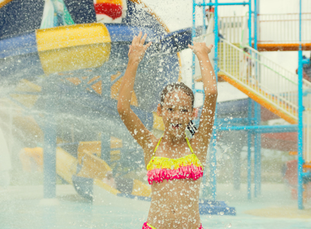 Cheerful preteen girl splashing water towards the camera. Blurred waterpark in background. Travel, fun, vacation concept. Text space Stock Photo