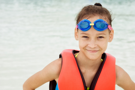 Happy preteen girl in life vest and swimming goggles against blurred water in water park. Look in camera. Travel, vacation background. Text space. Stock Photo