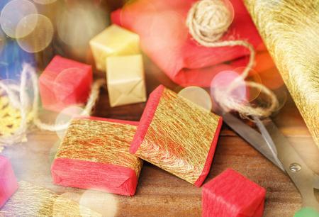 Červené a zlaté dárkové krabičky a řemeslný papír na dřevěném stole. Ručně vyrobené vánoční dárky pozadí. Zasněný efekt Reklamní fotografie