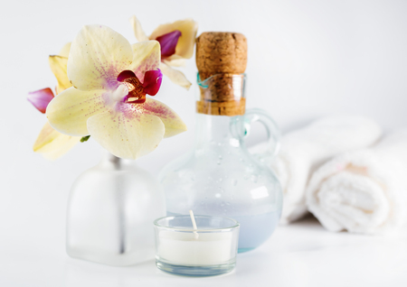 Aroma oil, orchid and candle on white table. Blurred towels in background. Healthy lifestyle, spa Stock Photo - 88173351