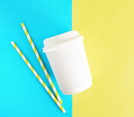 Flat ay top view white paper cup with colored disposable straw on colorful blue and yellow background. Mockup
