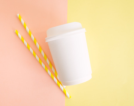 Flat ay top view white paper cup with colored disposable straw on colorful pink and yellow background. Mockup