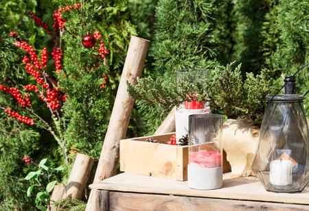 Christmas decoration at back yard background: cypress trees, candles, fir-cones on wooden table. New year preparation concept