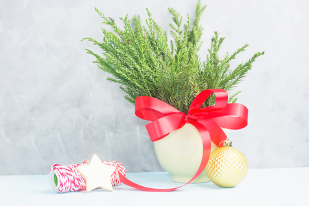 Green christmas tree branches with red bow in pot with wrapping tape and gold star against concrete grey wall. New year concept. Text space