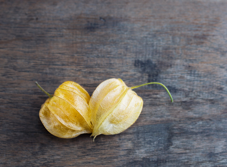 heart made from beautiful orange gooseberries on wooden rustic background. Vegetarian food concept. Detox