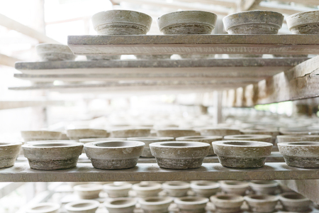 Handmade white clay pots dry on wooden planks. Workshop, manufactory interior Banque d'images - 122110508