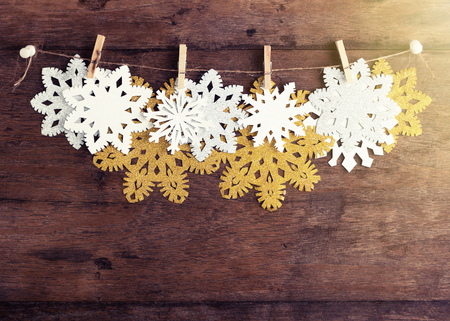 Golden, silver and white paper snowflakes with clothespin on twine on rustic wooden background. New year, christmas concept. Text space