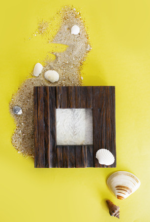 Empty photo frame with sea shells on sand over yellow paper. Travel, beach vacation concept. Text space.